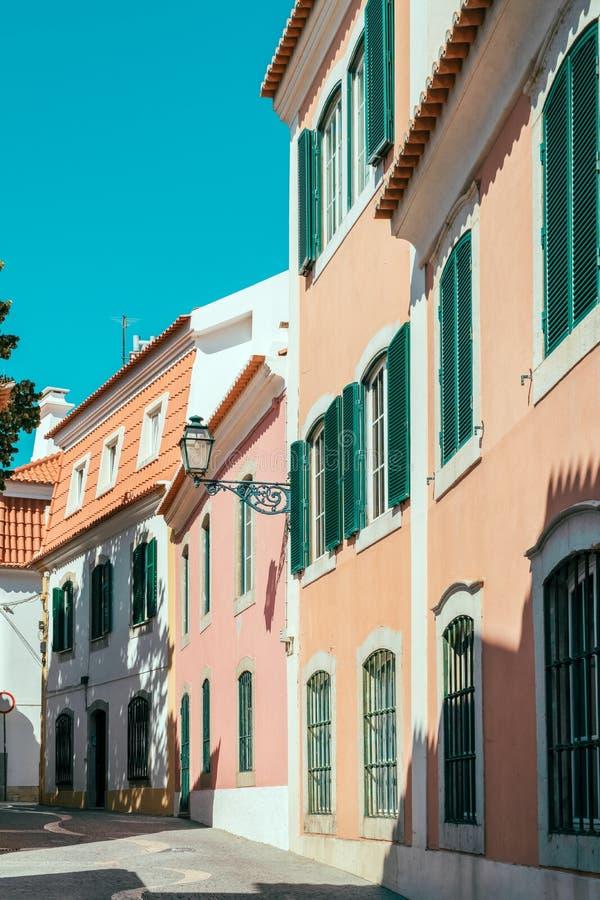 在狭窄的街道上的五颜六色的大厦在卡斯卡伊斯市,葡萄牙 免版税库存图片