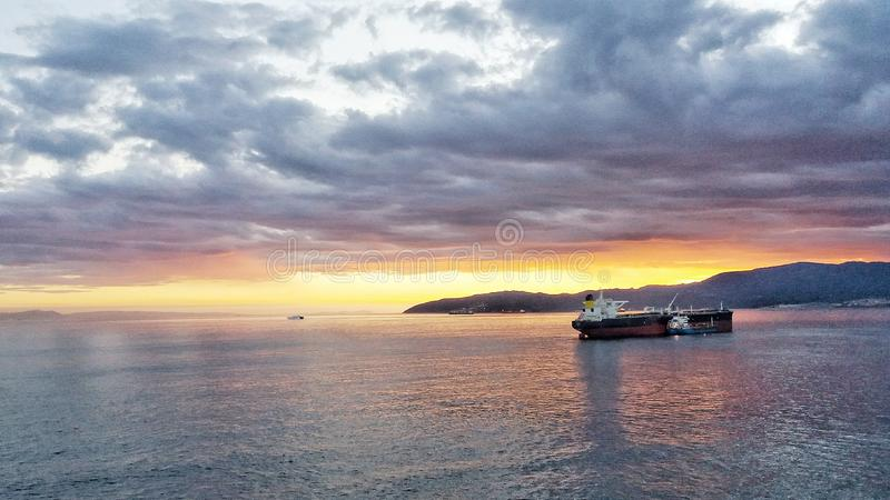 在直布罗陀海峡的太阳落山,罐车在海湾等待 免版税库存图片