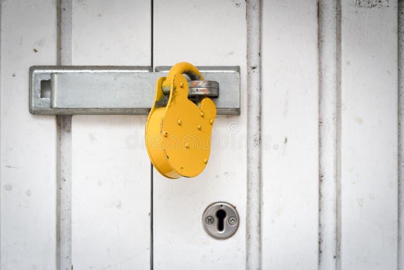 在白合金门安全背景的黄色挂锁 免版税库存照片