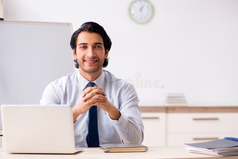 在白板前面的年轻英俊的财政speciaist 库存图片