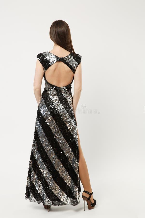 在白色墙壁上佩带典雅晚礼服黑色褂子摆在隔绝的时装模特儿妇女全长照片 库存照片