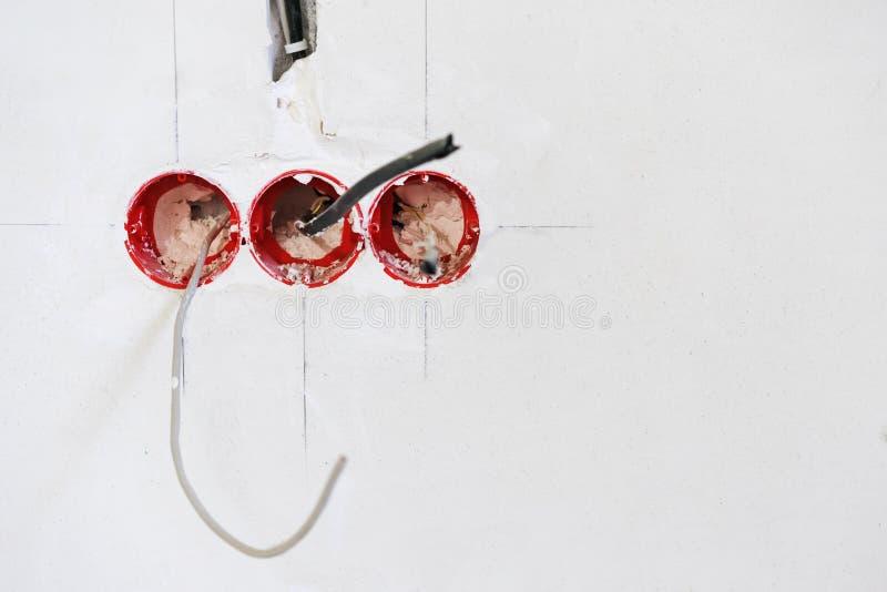 在白色墙壁上的电源插座在公寓修理  电子接线设施 库存照片