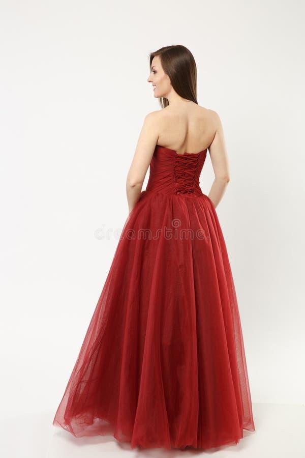 在白色墙壁背景佩带典雅晚礼服红色褂子摆在隔绝的时装模特儿妇女全长照片 免版税库存照片