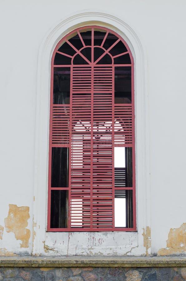 在白色大厦的红色窗口,未完成的窗口 免版税库存图片