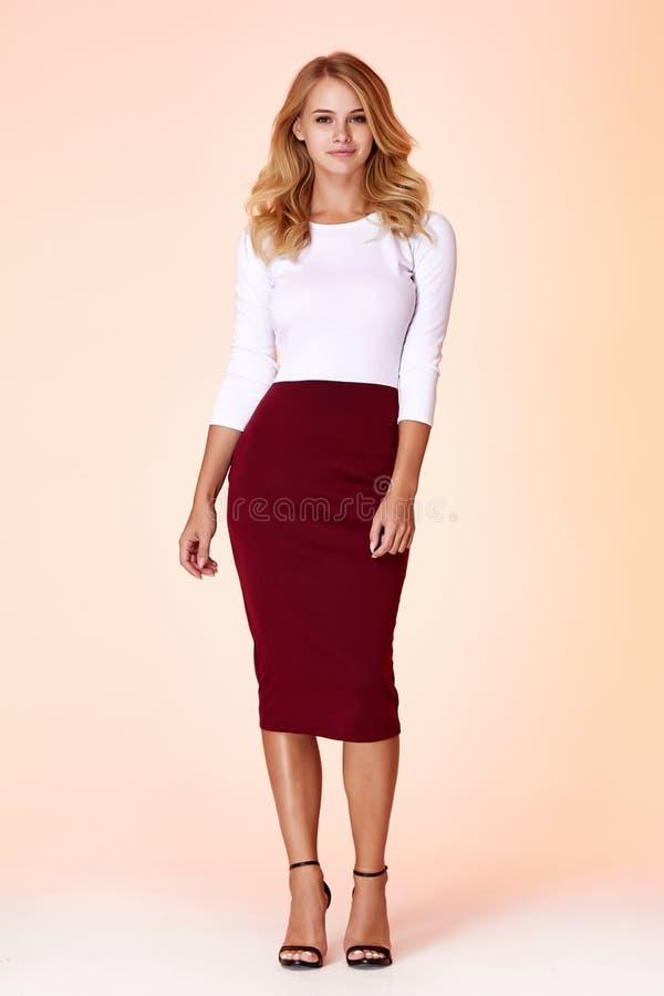 在白色女衬衫皮包骨头的裙子礼服背景演播室妇女金发构成身材衣裳的年轻美好的女性模型 免版税库存照片