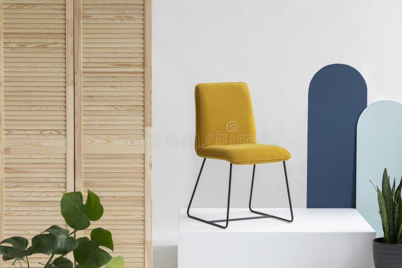 在白色平台的时髦黄色椅子在与蓝色墙壁、木屏幕和绿色植物的白色和明亮的内部 库存图片
