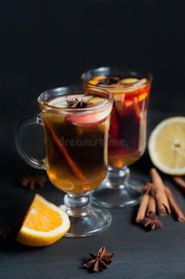 在白色土气杯子的被仔细考虑的酒用香料和柑橘水果 库存图片