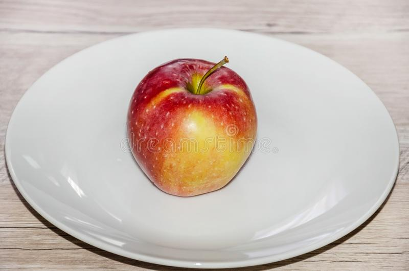 在白色板材的小红色苹果在灰色桌上 图库摄影