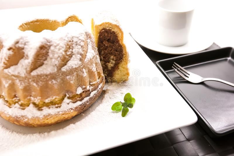 在白色板材的被切的大理石bundt蛋糕 免版税图库摄影