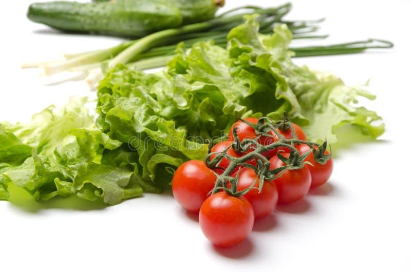 在白色桌上的鲜美和成熟菜 沙拉的成份 蕃茄、莴苣、黄瓜和大葱 图库摄影