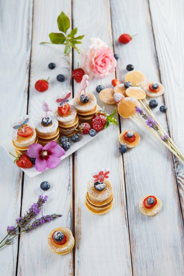 在白色木桌上的果子、莓果和薄煎饼点心 免版税库存照片