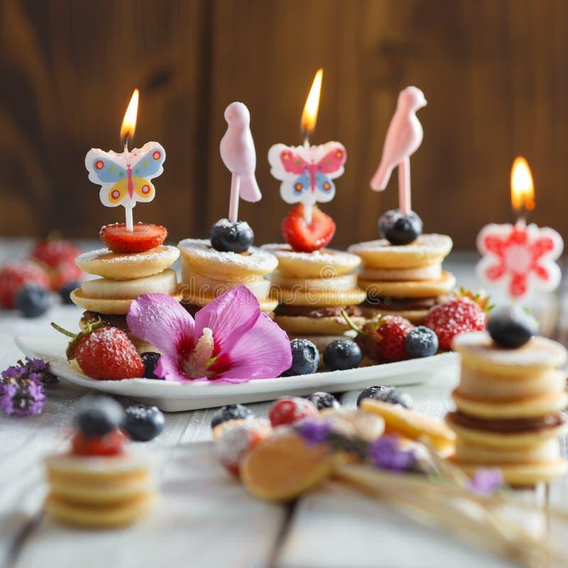 在白色木桌上的果子、莓果和薄煎饼点心 库存照片