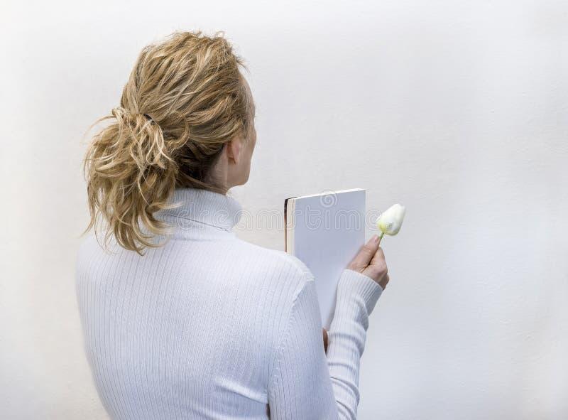 在白色打扮的白肤金发的妇女拿着书和一束白花反对完全地白色背景 免版税库存照片
