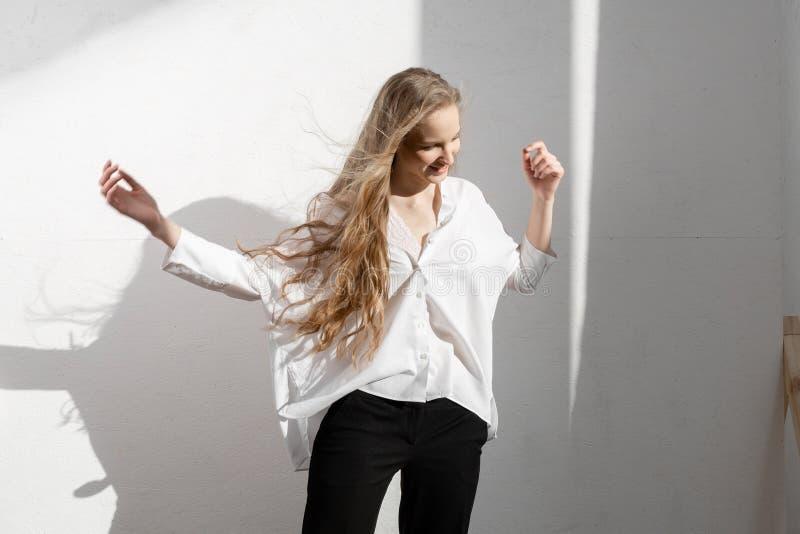 在白色衬衫和黑长裤的美好的新白肤金发的模型 库存图片