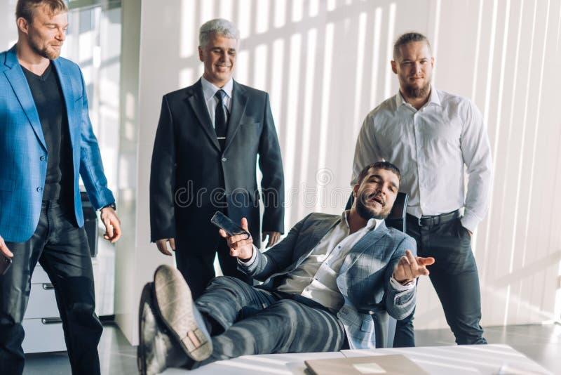 在白色衬衫的乐观商人合作与他的队的在见面 库存照片