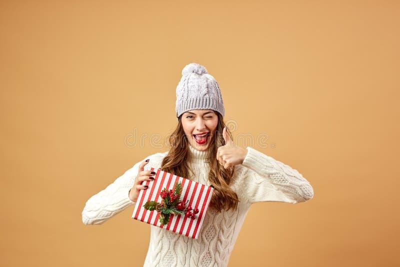 在白色被编织的毛线衣和帽子打扮的微笑的女孩在演播室拿着在米黄背景的一圣诞礼物 库存图片