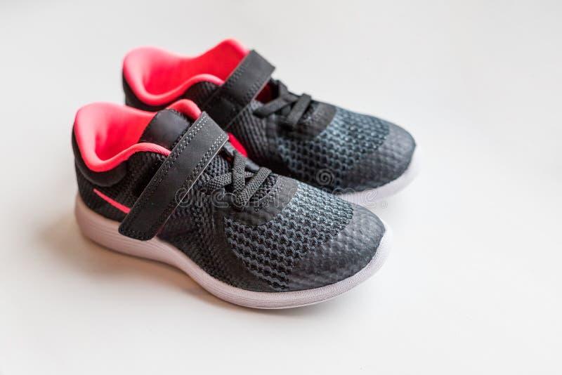 在白色背景的婴孩运动鞋,孩子运动鞋 连续运动鞋 小儿童体育黑色鞋子隔绝了 孩子 库存图片