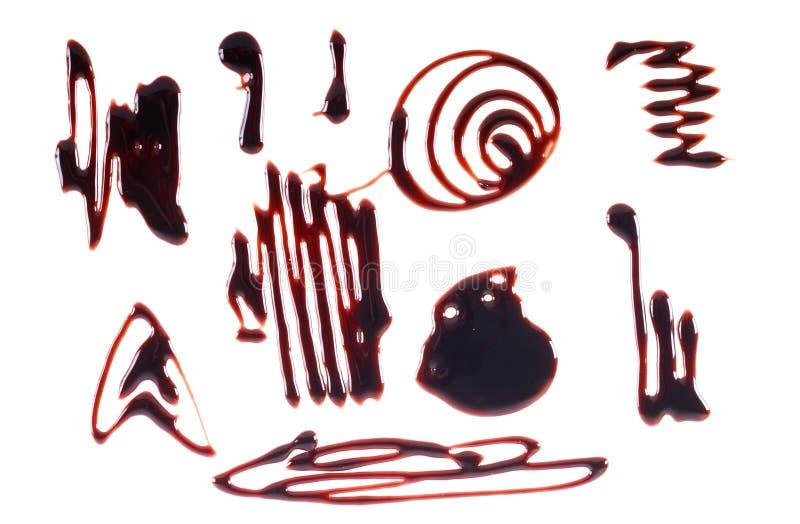在白色背景的巧克力糖浆毛毛雨 免版税库存图片