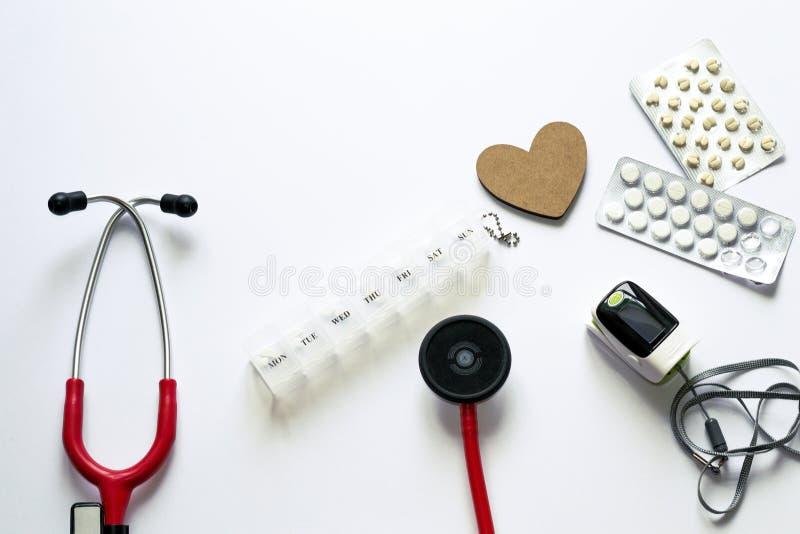 在白色背景的医疗flatlay构成 对待心脏疾患 复杂化的预防 生命维持设备 免版税库存图片