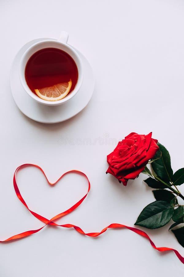 在白色背景的红色玫瑰,丝带在ide的心脏在3月8日前 免版税库存图片