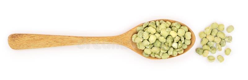 在白色背景隔绝的一把木匙子的绿色分裂豌豆 顶视图 免版税库存照片