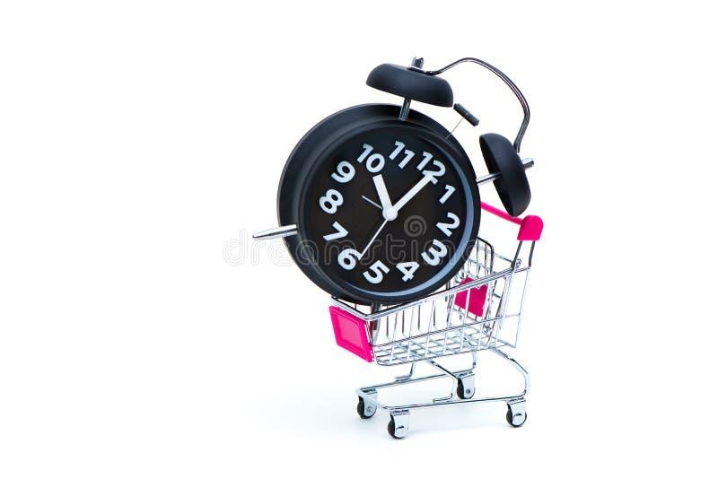 在白色背景隔绝的黑闹钟和手推车或者超级市场台车,企业财务购物概念,苏醒 库存照片