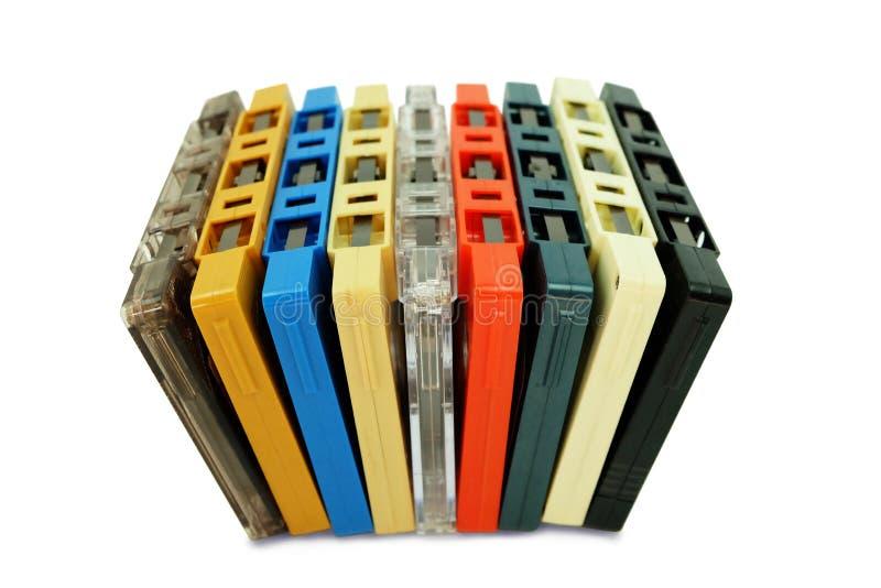 在白色隔绝的五颜六色的老卡型盒式录音机磁带行  库存照片