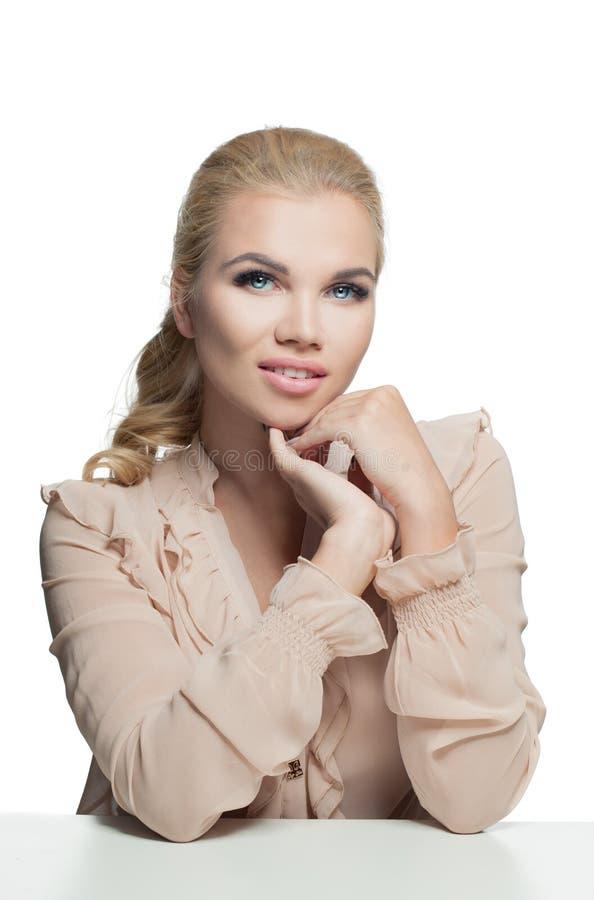 在白色隔绝的桃子颜色柔滑的女衬衫的美丽的白肤金发的妇女 库存图片