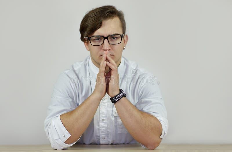 在白色长袍的年轻白种人严肃的男性坐皱眉,在桌上的手 感觉神色,强的情感 电子手表 免版税库存照片