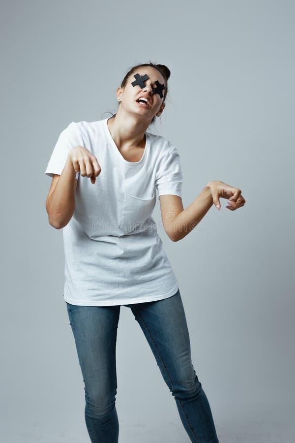 在白色T恤和牛仔裤打扮的少女有橡皮膏黑十字架的在眼睛在白色站立 库存图片