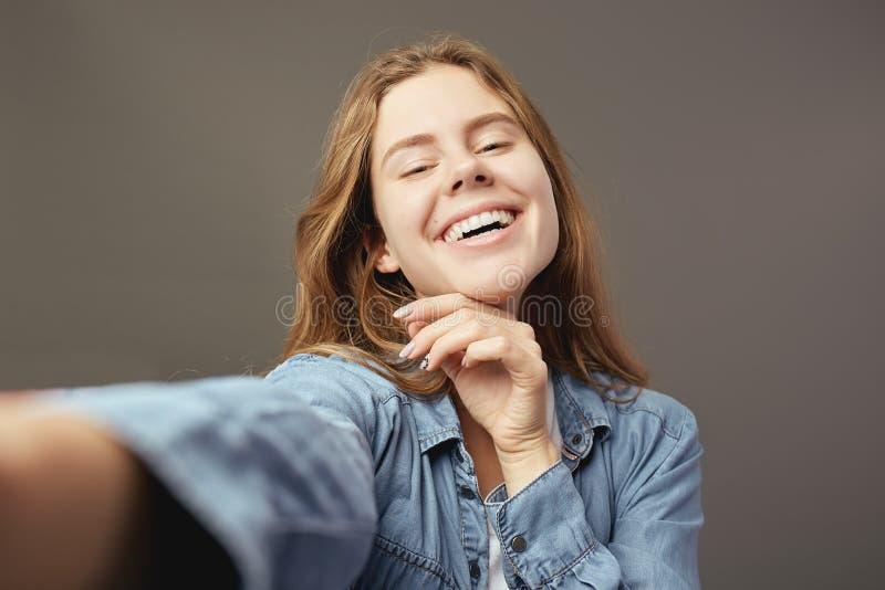 在白色T恤和牛仔裤衬衣打扮的微笑的棕色毛发的女孩在灰色背景做一selfie 免版税库存图片