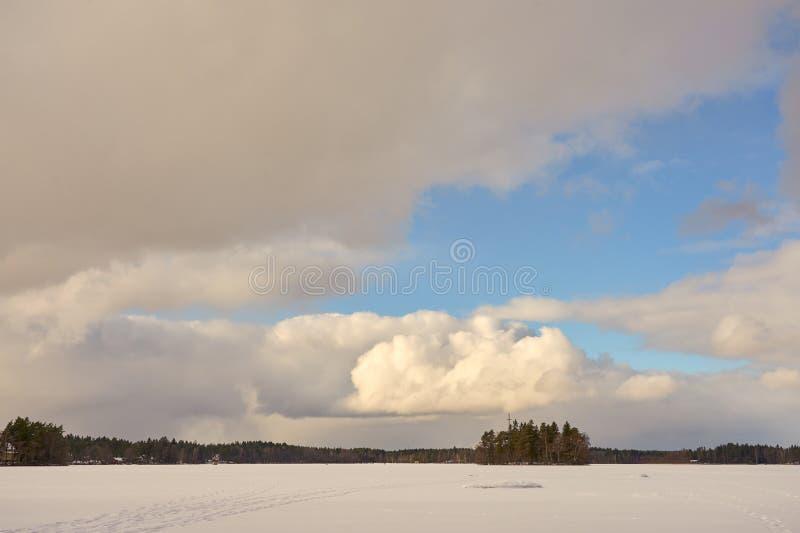 在用冰和雪盖的LittoistenjA¤rvii湖中间的海岛在蓝色多云天空下 免版税库存照片