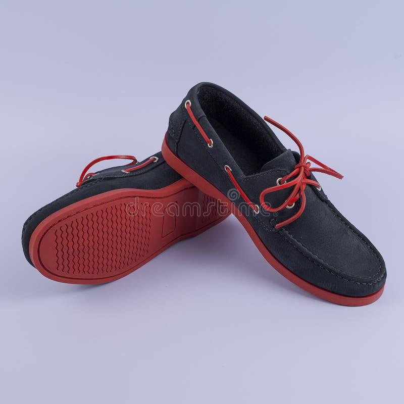 在紫色背景隔绝的人的深蓝游手好闲者鞋子 免版税库存图片