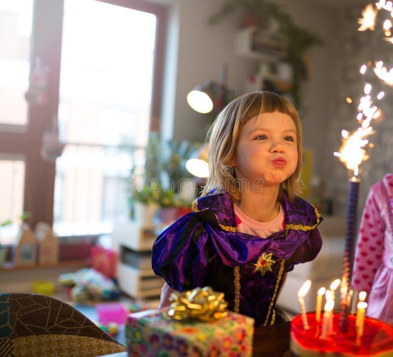 在生日蛋糕的女孩吹的蜡烛 免版税库存图片