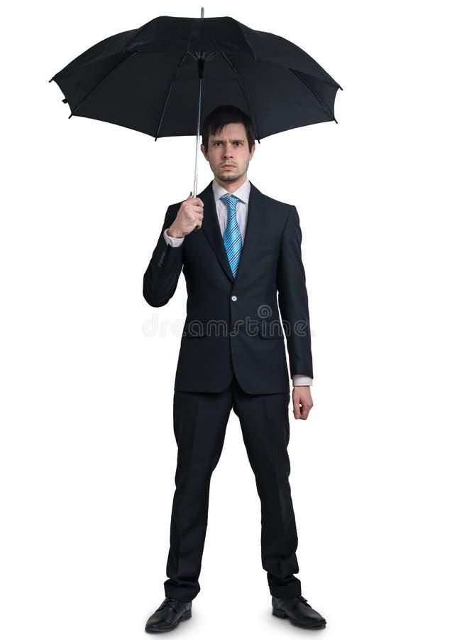 在衣服的年轻商人与在白色背景隔绝的伞 免版税库存照片