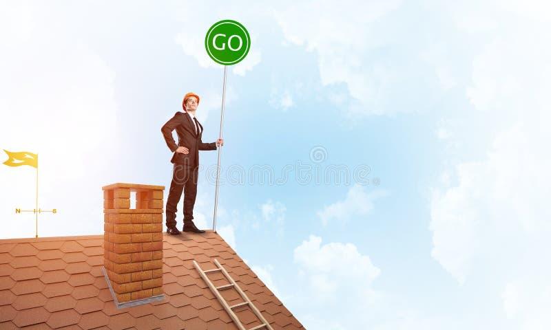 在衣服的商人在与生态概念牌的房子上面 混合画法 免版税图库摄影