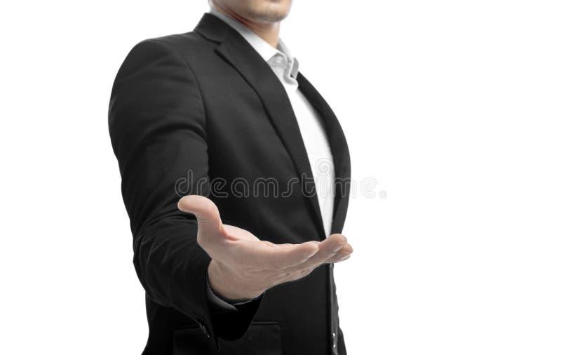在衣服身分的商人与提议握手和举行或者显示的某事开放棕榈 免版税图库摄影
