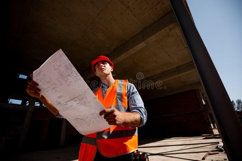在衬衣、橙色工作背心和盔甲打扮的年轻人探索建筑工地的建筑文献里面 库存照片