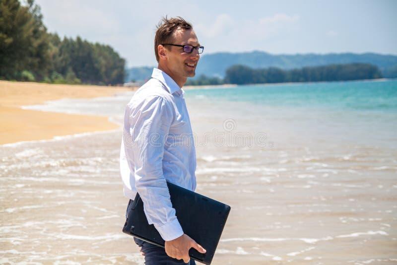 在衬衣的愉快的商人有膝上型计算机的和有玻璃的走在海滩的 免版税图库摄影