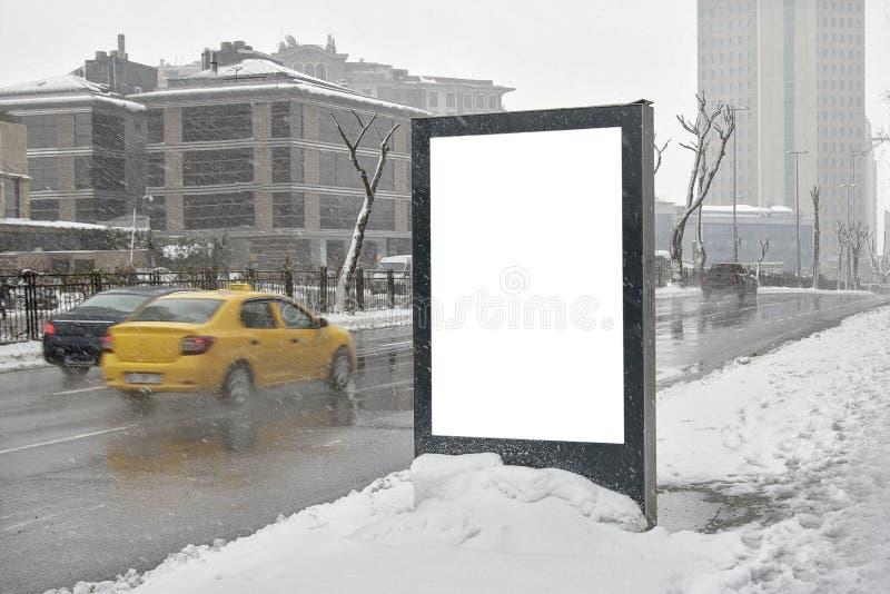 在街道上的广告牌在冬天 免版税库存图片