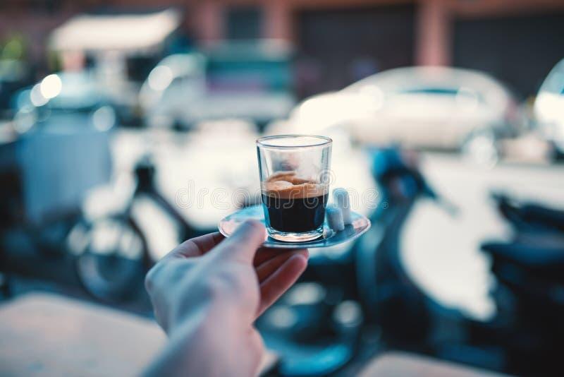 在街道上的浓咖啡咖啡在马拉喀什-摩洛哥 拿着一个杯子在铁板材的新酿造的coffe的人用糖 库存照片