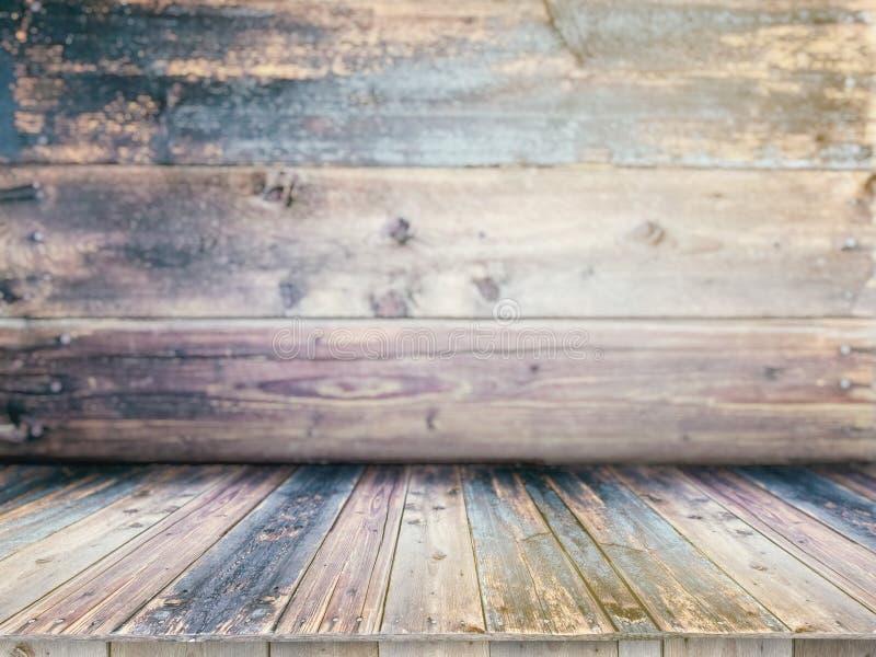 在被弄脏的背景前面的木板空的桌 免版税库存照片