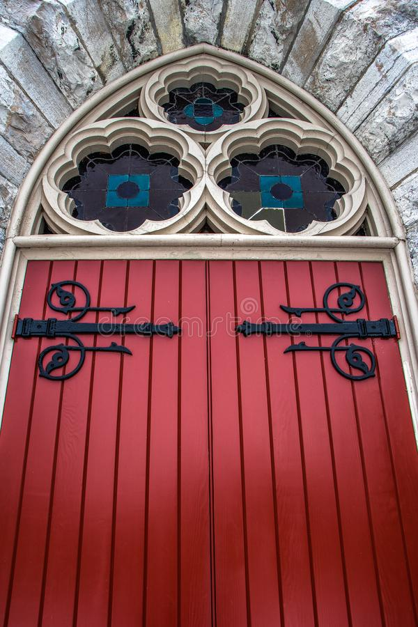 在被成拱形的入口的红色木门对19世纪教会 库存照片