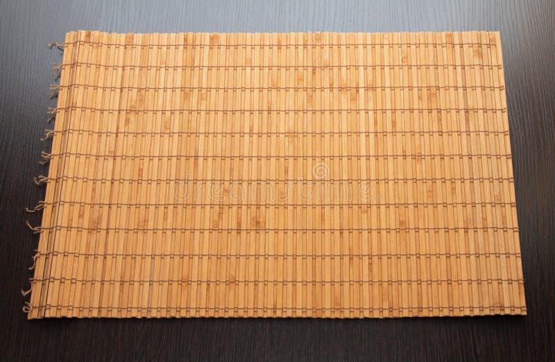 在被隔绝的黑暗的木背景的竹餐巾 库存照片