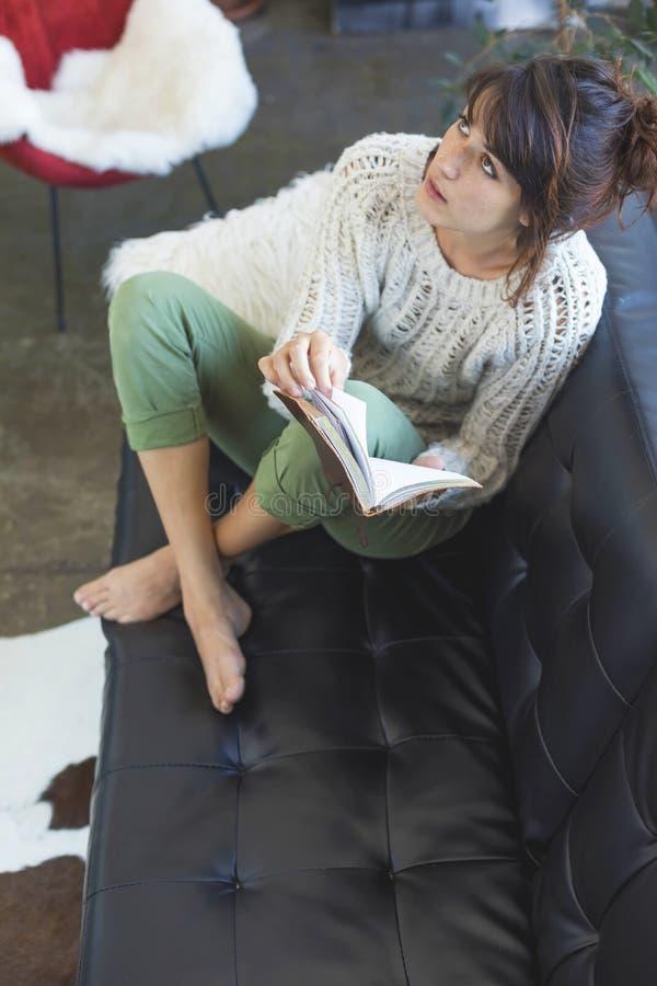 在观点的美丽的年轻微笑的妇女上坐放松皮革的长沙发,当在家时拿着书 免版税库存图片