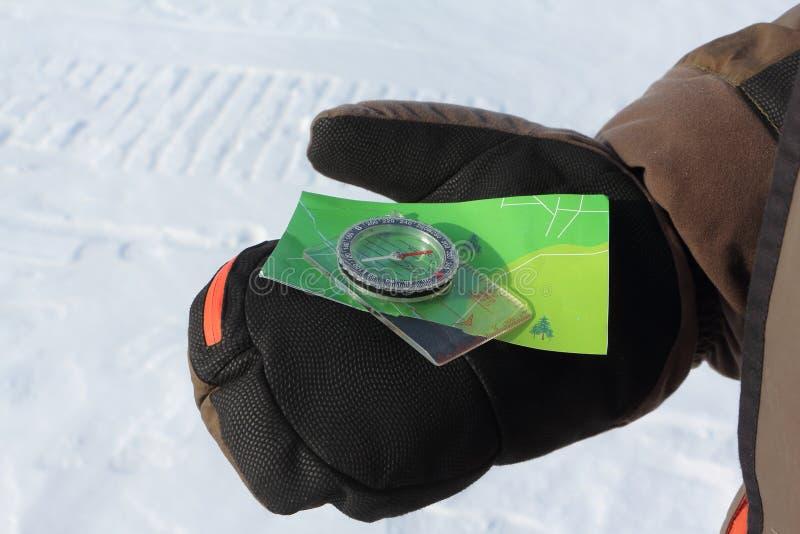 在说谎在一个手套的手上的地图的指南针在雪背景  免版税库存照片