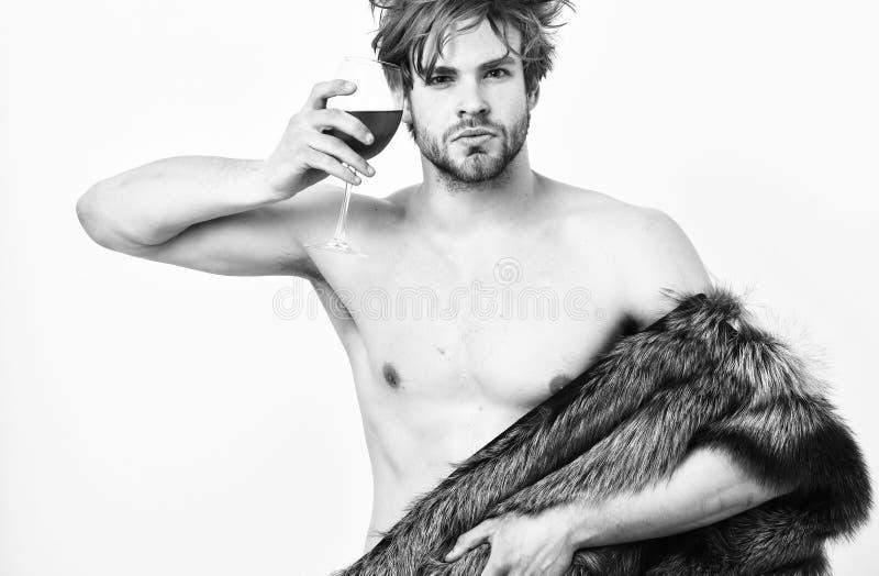 在赤裸身体的人有吸引力的富有的摆在的毛皮大衣 富有的运动员享有他的生活 丰厚和豪华概念 性感困 免版税库存图片