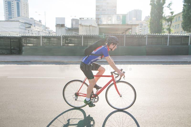 在路乘坐在城市运动员骑自行车者的画象 体育概念 图库摄影