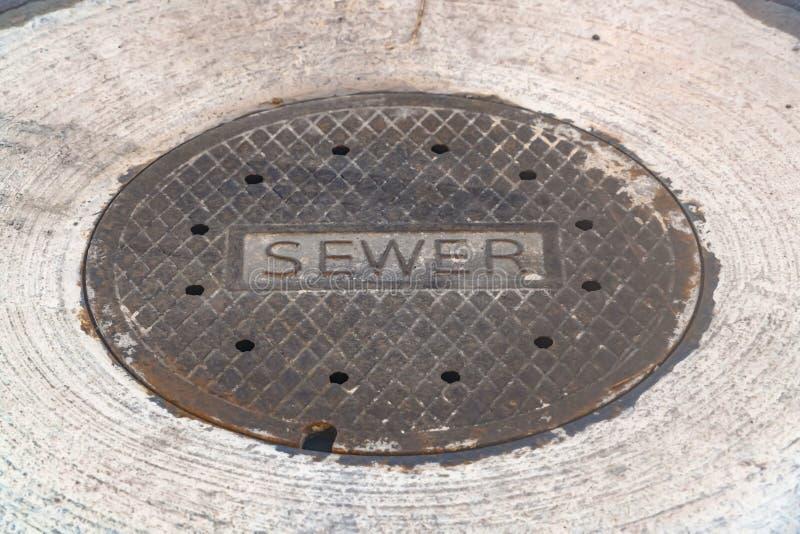 在路的被风化的下水道人孔盖 免版税库存照片