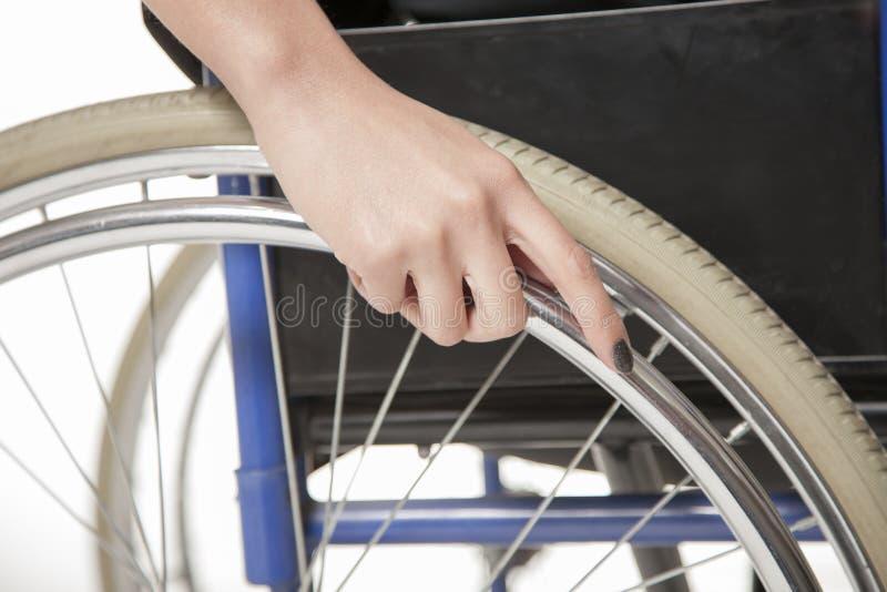 在轮椅的轮子的女性手 免版税库存照片